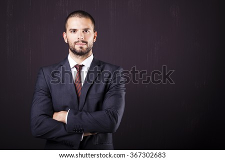 Handsome businessman with crossed arms against dark background - stock photo