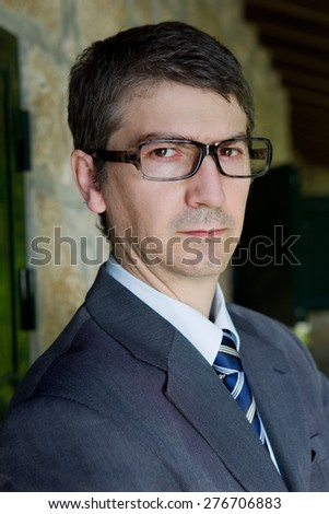 handsome businessman with glasses outdoors - stock photo