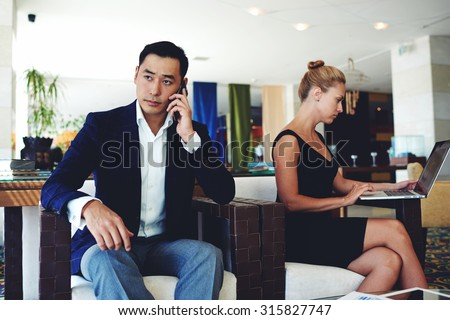 Handsome businessman with serious face discussing work issues by mobile phone, young smart woman working on laptop computer, successful male and female entrepreneurs sitting in modern office interior - stock photo