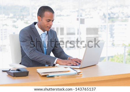 Handsome businessman working at his laptop in his office - stock photo