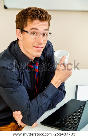 Handsome businessman working at the office on his laptop and friendly smiling at camera. - stock photo