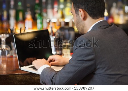 Handsome businessman working on his laptop while having a drink in a classy bar - stock photo
