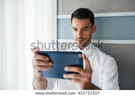 Handsome businessman working, searching and reading on the device, gadget in the office. Business. - stock photo