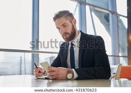 Handsome businessman writing notes from smartphone at modern office - stock photo