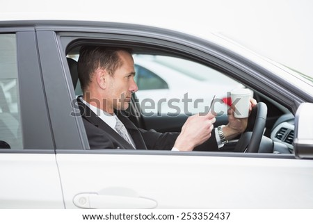 Handsome businesswoman having a coffee in his car - stock photo