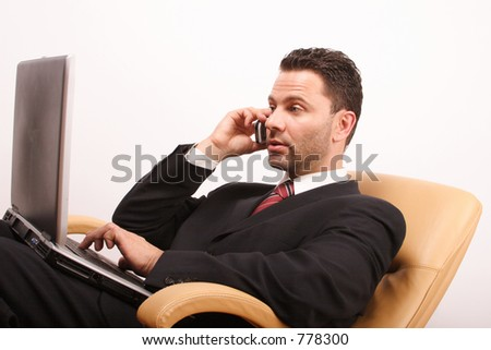 Handsome calling businessman with laptop sitting on leather armchair - stock photo