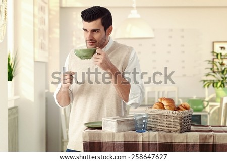 Handsome casual caucasian man drinking morning breakfast tea at vintage home with tea cup and spoon in hand. Wearing sleeveless sweater, standing at dining room, wondering, thinking, smiling, bristly. - stock photo
