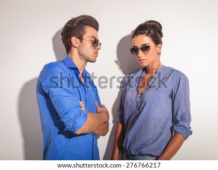 Handsome casual man leaning on a grey wall while looking at this lover. - stock photo