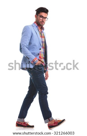 Handsome casual man looking at the camera while walking with his hand in pocket. - stock photo