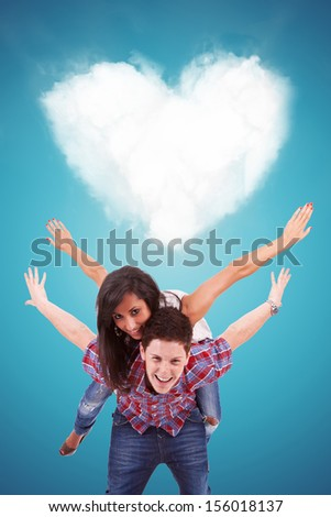 Handsome casual young man carrying his girlfriend on his back, playing in front of a heart shaped cloud - stock photo