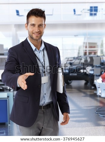 Handsome caucasian businessman shaking hands on successful deal at car saloon. Smiling, happy, looking at camera, wearing suit and name tag, clipboard under arm, hand outstretched. - stock photo