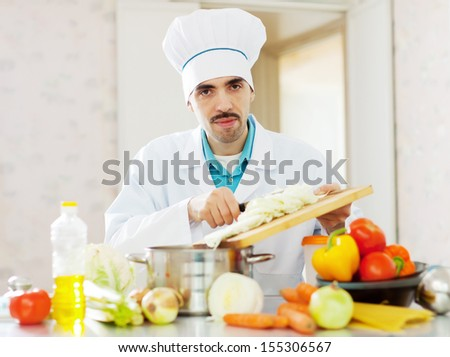 Handsome caucasian cook does veggie lunch at kitchen - stock photo