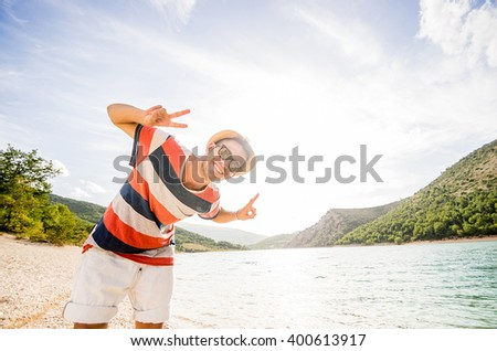 Handsome caucasian hiker is smiling at the beach - caucasian people - people, nature and lifestyle concept - stock photo