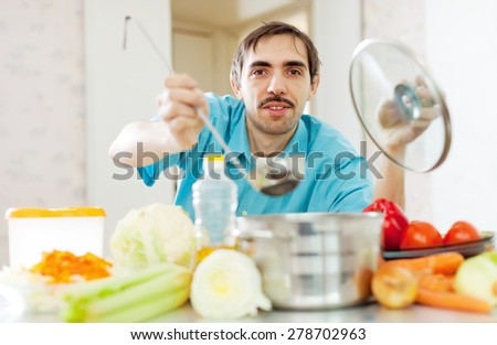 handsome caucasian man cooking with ladle in kitchen - stock photo