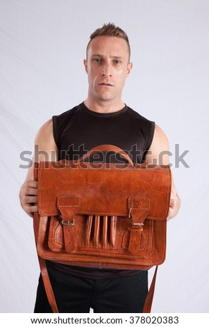 Handsome Caucasian man holding a leather briefcase - stock photo
