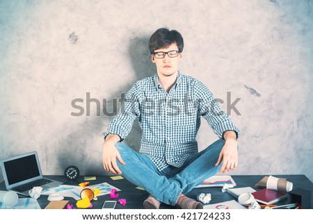 Handsome caucasian man meditating on messy desktop with blank laptop screen on concrete wall background. Mock up - stock photo