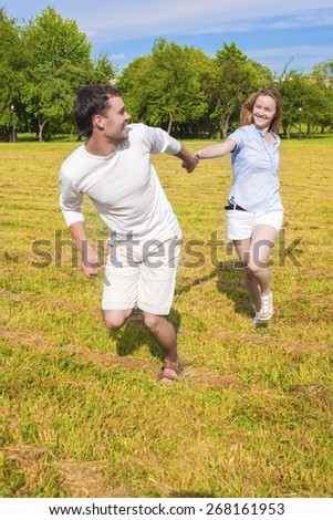 Handsome Caucasian Man Pulling Her Smiling Lady by Hand. Couple Spending Their Holiday Time Together Outside. Vertical Image Composition - stock photo