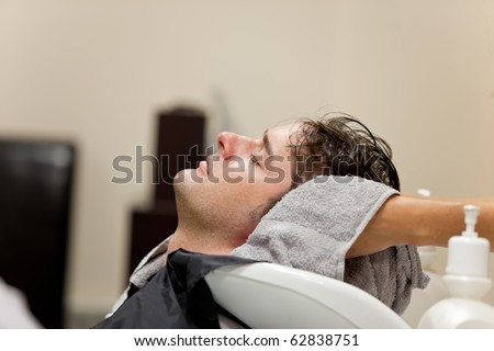 Handsome caucasian man shampooed in a hairdressing salon - stock photo
