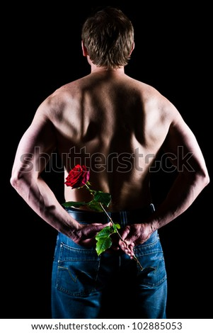 Handsome caucasian man to keep a rose behind his back - stock photo