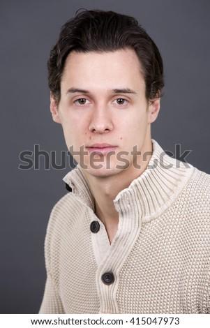 handsome caucasian man wearing beige sweather on grey background - stock photo