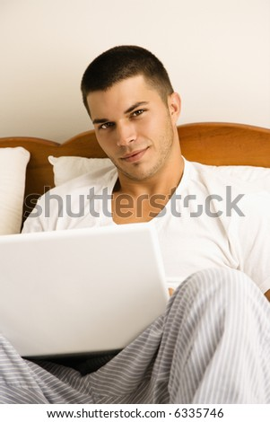 Handsome Caucasian mid adult man sitting in bed with laptop looking at viewer. - stock photo