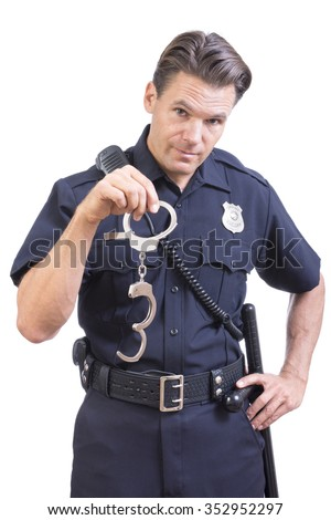 Handsome Caucasian police officer dangles pair of handcuff restraints in one hand as a warning on white background - stock photo