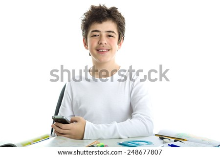 Handsome Caucasian smooth-skinned boy sits in front of homework wearing a white long sleeve t-shirt and smiles using his cell phone, a smartphone - stock photo