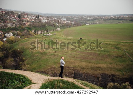 Handsome caucasian young man in casual clothes in urban environment. He is standing on the cliff and looking into the distance - stock photo