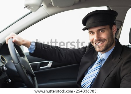 Handsome chauffeur smiling at camera in the car - stock photo