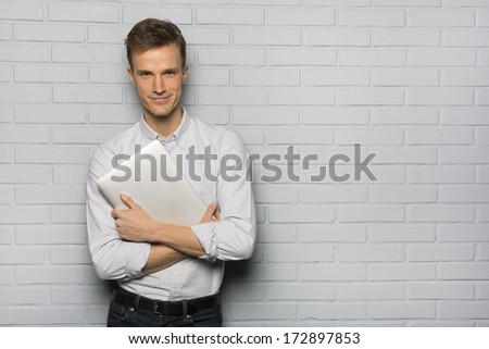 Handsome Cheerful man holding a laptop, isolated over a gray brick wall - stock photo