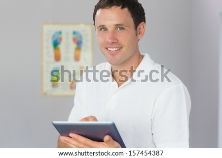 Handsome cheerful physiotherapist holding tablet in bright office - stock photo
