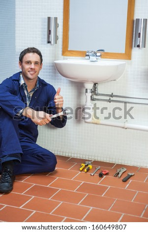 Handsome cheerful plumber sitting next to sink showing thumb up in public bathroom - stock photo