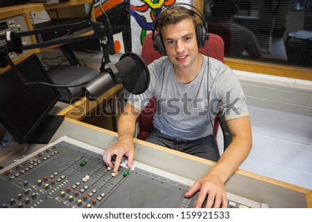 Handsome cheerful radio host moderating sitting in studio at college - stock photo