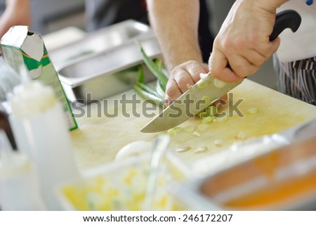 Handsome chef dressed in white uniform decorating pasta salad and seafood fish in modern kitchen - stock photo