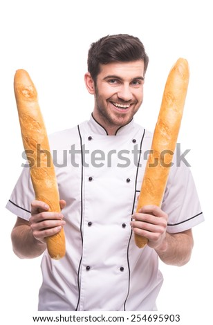 Handsome chef is holding a baguettes, isolated on white background. - stock photo