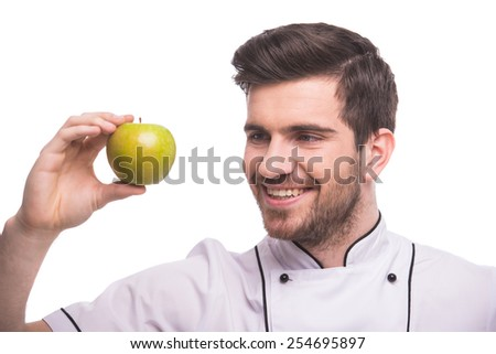Handsome chef is holding an apple, isolated on white background. - stock photo