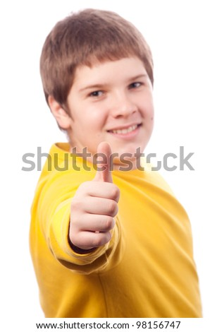Handsome chubby teenage boy showing thumbs up. Selective focus is on the thumb. - stock photo