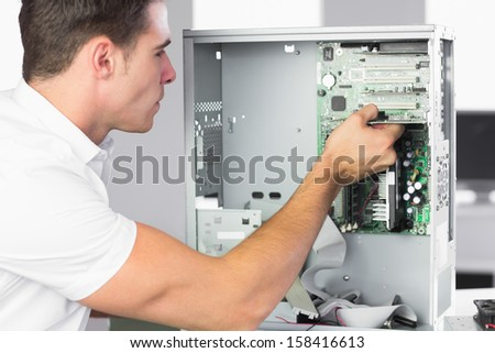 Handsome computer engineer working at open computer in bright office - stock photo