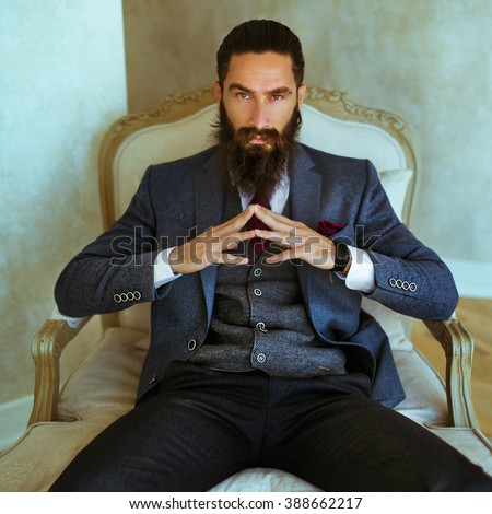 Handsome confident bearded man sitting in luxury white chair - stock photo