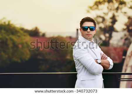 Handsome confident brunette groom in sunglasses at sunset closeup - stock photo