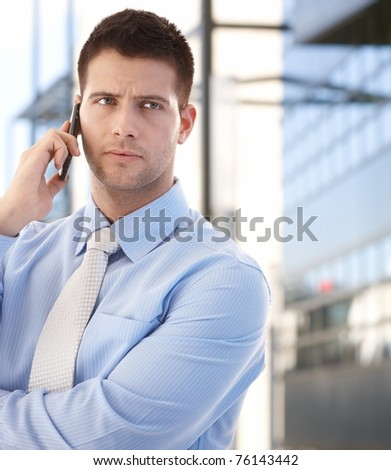 Handsome confident businessman talking on mobile phone in business quarter.? - stock photo