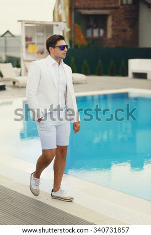 Handsome confident groom in sunglasses and white suit walking near a pool at resort - stock photo