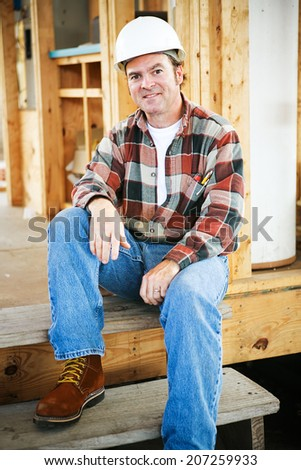 Handsome construction worker taking a break on the job site.   - stock photo