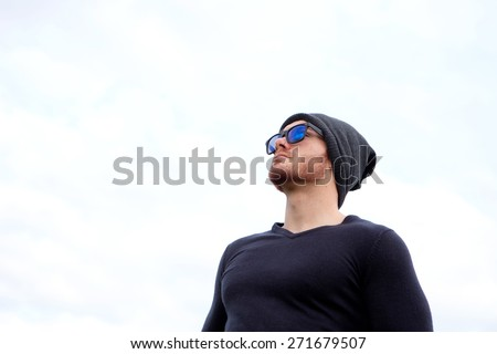 Handsome cool man with cap wool looking away - stock photo