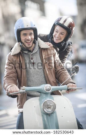 handsome couple riding a trendy scooter - stock photo