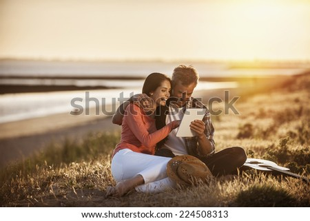 handsome couple sitting on the beach at sunset and using a digital tablet - stock photo