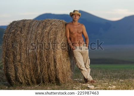 Handsome Cowboy lean on a hay bale with mountains background - stock photo
