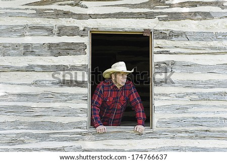 Handsome cowboy or rancher looking off into the distance from a rustic window - stock photo