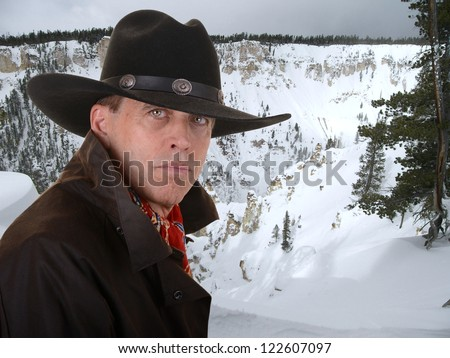 Handsome cowboy wearing a red scarf against a snowy winter canyon - stock photo