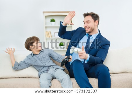Handsome dad enjoying time with cute son - stock photo